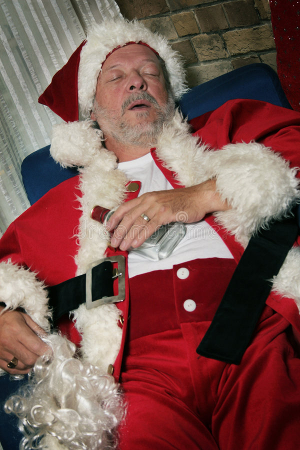 Santa Clause sleeps. Santa clause is sleeping holding alcohol in his hand and beard in the other royalty free stock photos