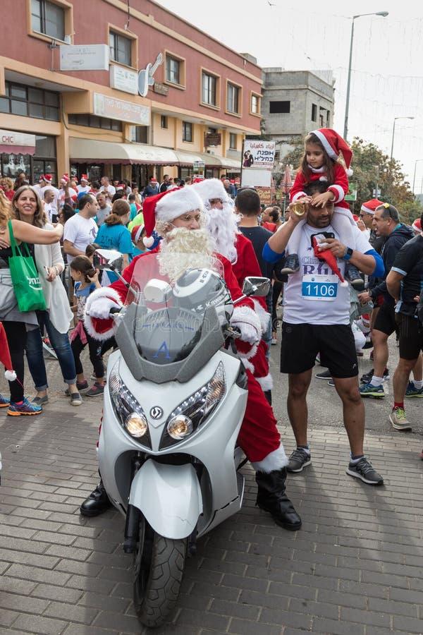 Santa Clauses em um passeio do 'trotinette' de motor entre os participantes e os visitantes do ` anual Cristmas da raça correm o  imagem de stock
