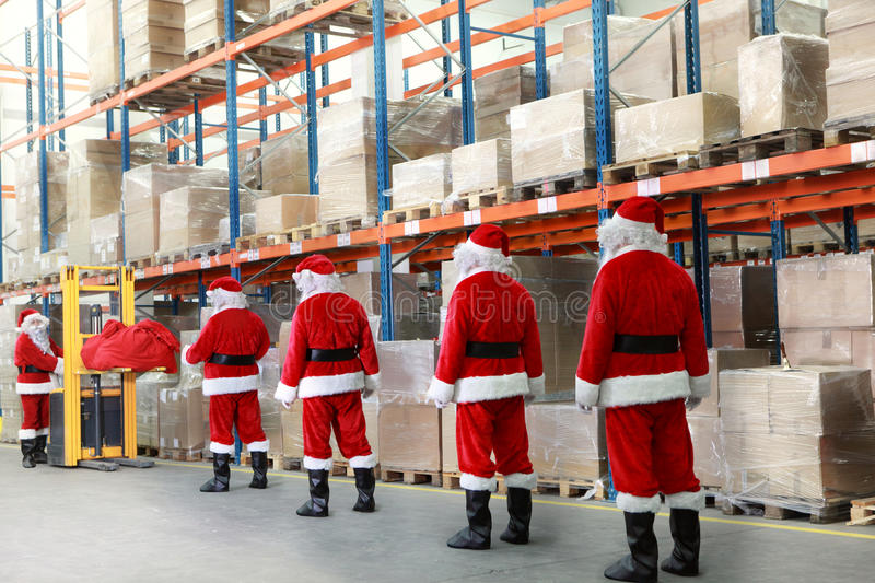 Santa clauses in the line for gifts in warehouse. Santa clauses in the line for the sacks of gifts in storehouse stock image