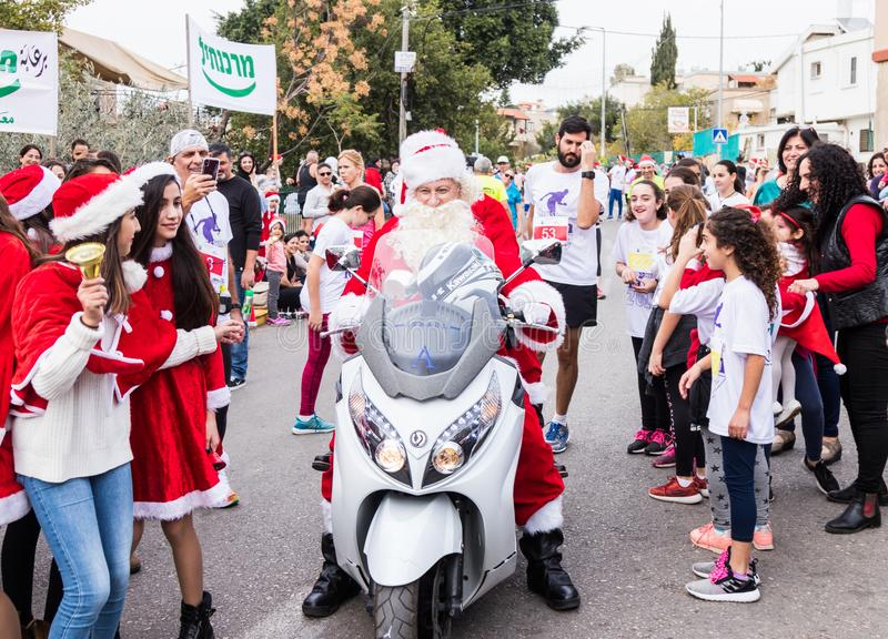 Santa Clauses on a motor scooter ride among the participants and visitors of the annual race `Cristmas Run` in Mi`ilya in Israel. Mi`ilya, Israel, December 22 royalty free stock image