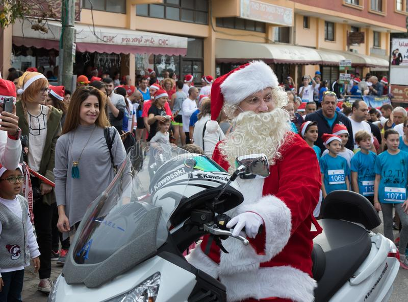 Santa Clauses on a motor scooter ride among the participants and visitors of the annual race `Cristmas Run` in Mi`ilya in Israel. Mi`ilya, Israel, December 22 stock photos