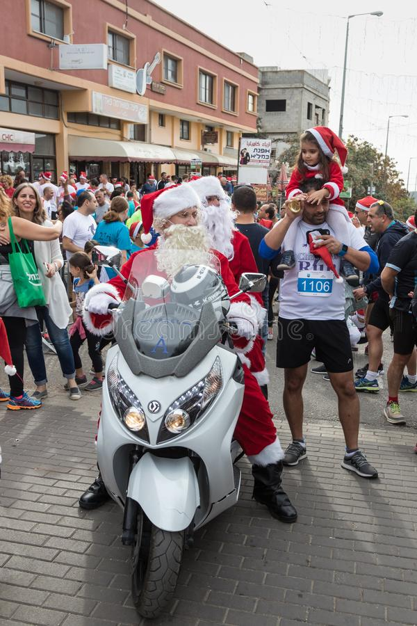 Santa Clauses on a motor scooter ride among the participants and visitors of the annual race `Cristmas Run` in Mi`ilya in Israel. Mi`ilya, Israel, December 22 stock image