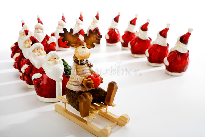 Santa Clauses queuing at sledge with elk. On white background stock photos