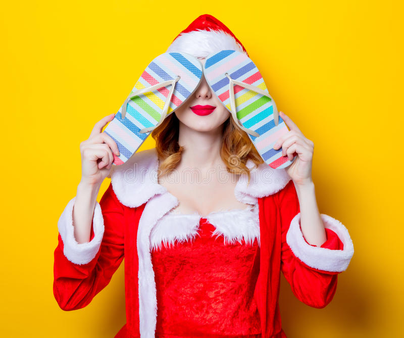 Santa Clous girl in red clothes with flip flops. Portrait of Young Santa Clous girl in red clothes with flip flops on yellow background royalty free stock image
