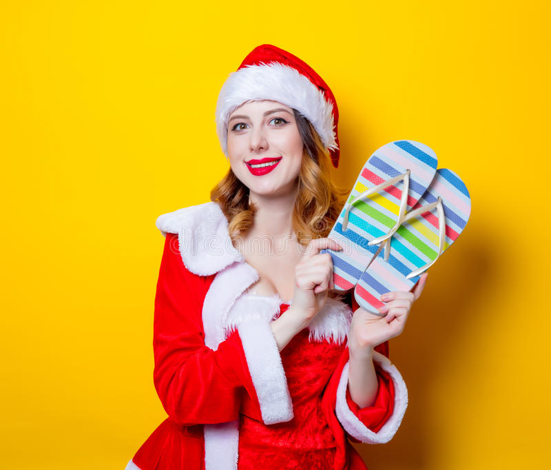 Santa Clous girl in red clothes with flip flops. Portrait of Young Santa Clous girl in red clothes with flip flops on yellow background royalty free stock photo