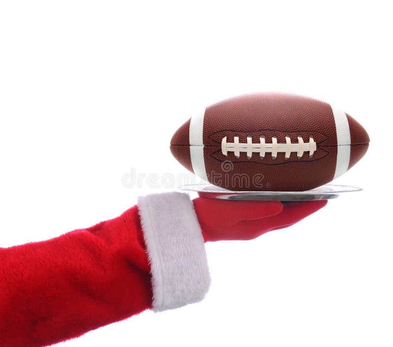 Santa com a bandeja do futebol americano fotografia de stock