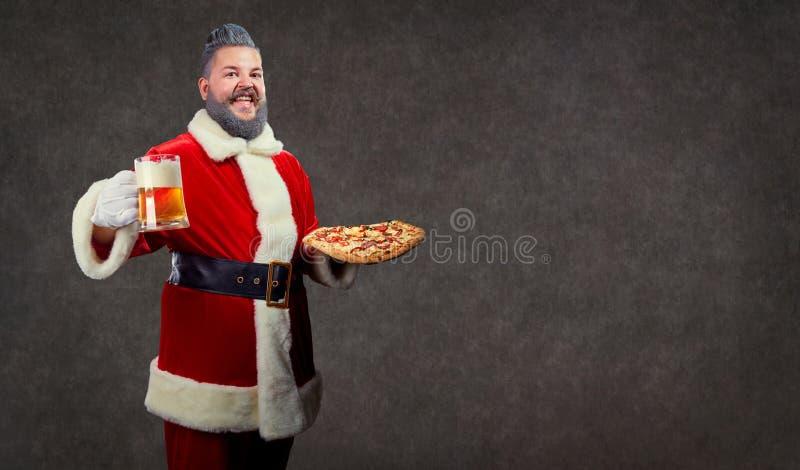 Santa com pizza e um vidro da cerveja em suas mãos fotografia de stock royalty free