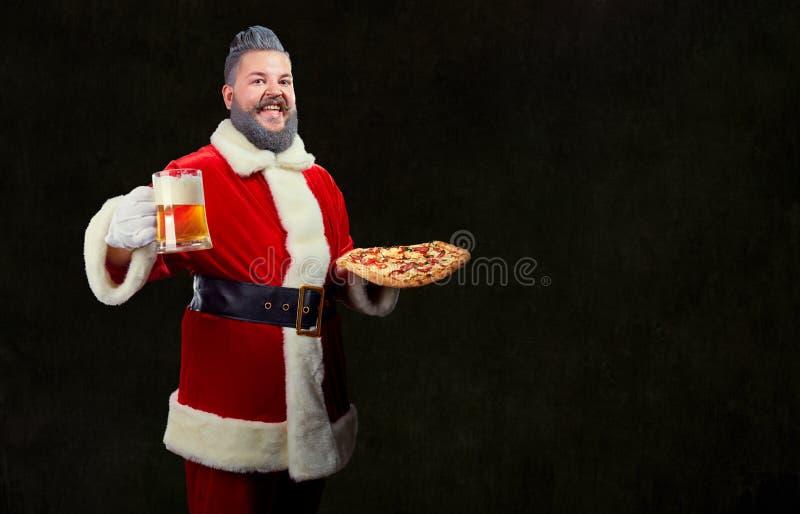 Santa com pizza e um vidro da cerveja em suas mãos no Natal imagem de stock royalty free