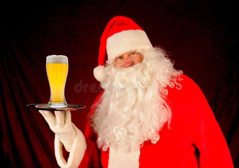 Santa con el vidrio de cerveza en la bandeja fotos de archivo libres de regalías
