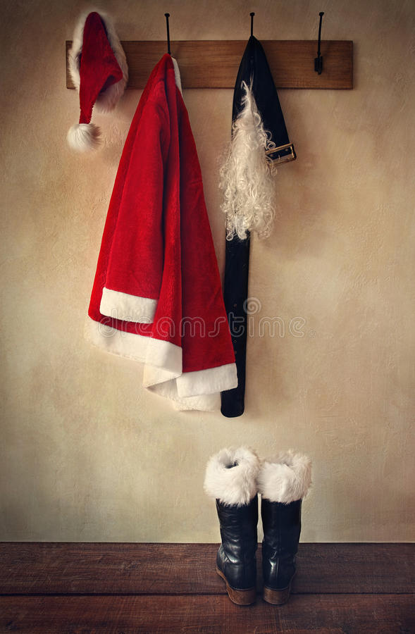 Santa costume with boots on coatrack stock images