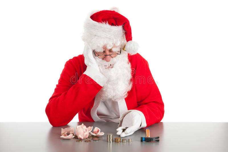Santa counting coins. Santa had damaged his piggy bank and is counting poor money stock photography