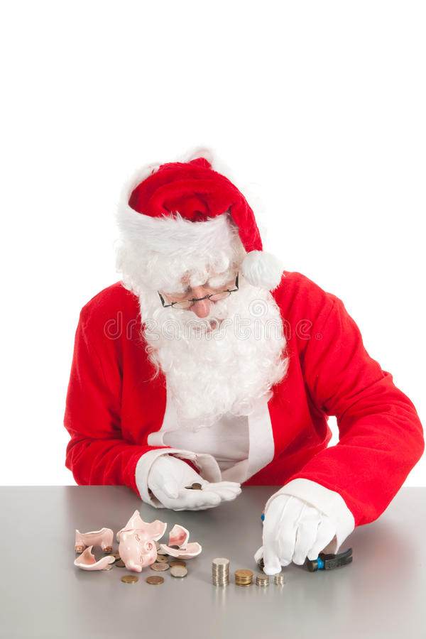 Santa counting coins. Santa had damaged his piggy bank and is counting poor money royalty free stock image