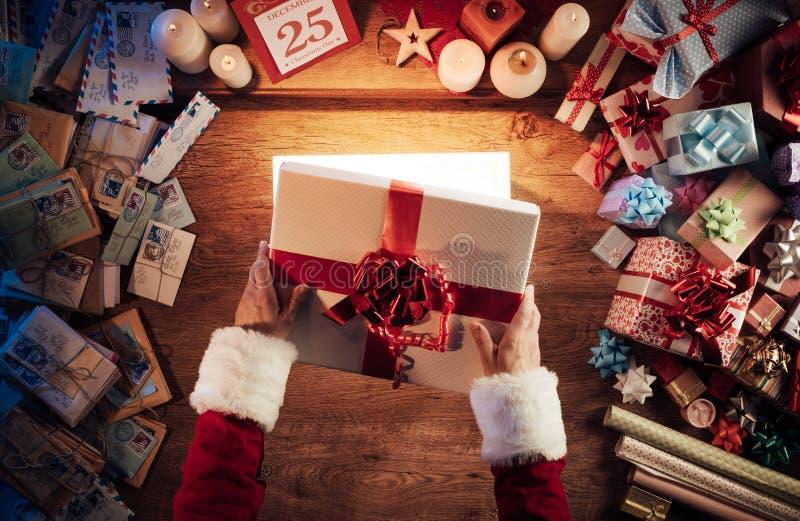 Santa die een giftdoos opent stock fotografie