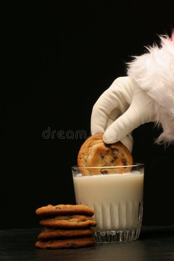 Santa dips a cookie in the milk royalty free stock photos