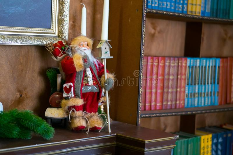 Santa doll on the table with candles in the library. Book is the background selective focus. New year concept stock images