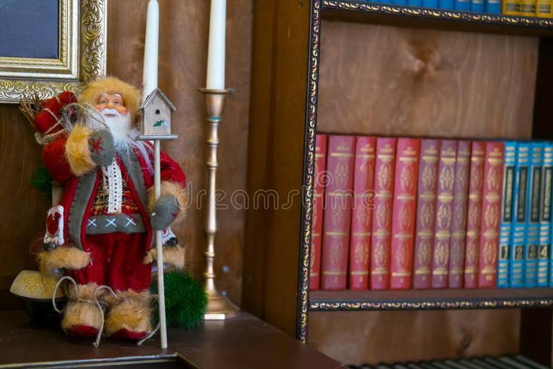 Santa doll on the table in the library. Book is the background selective focus. New year concept stock images