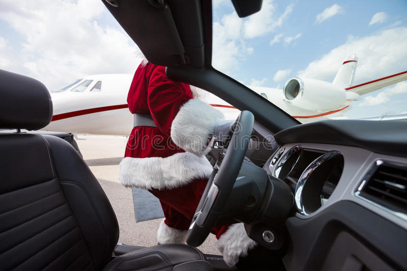 Santa Driving Convertible At Airport terminal royaltyfria foton