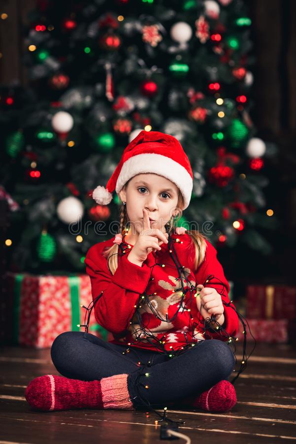 Santa dziewczyna zawijająca w girlandzie i przedstawieniach shhh fotografia stock
