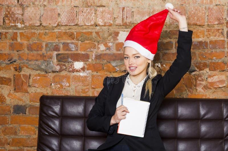Santa dziewczyny bizneswoman z notatnikiem i laptopem przy loft biurem na rzemiennej leżance w kostiumu pojęcia prowadzenia domu  zdjęcia royalty free