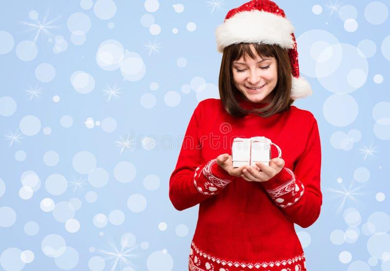 Santa dziewczyny mienia bożych narodzeń prezent nad wakacjami zaświeca backgroun obraz stock