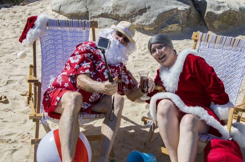 Santa e Sra. Claus que toma o selfie com a vara na praia imagem de stock