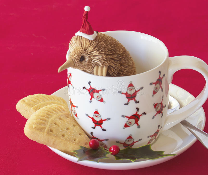 Santa Echidna in Christmas Cup with Shortbread. An echidna wearing a Santa hat, looks over the edge of a Christmas cup at the pieces of shortbread below royalty free stock images