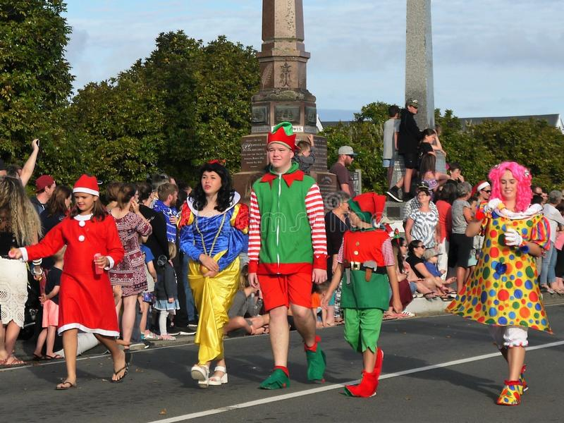 New Zealand: small town Christmas parade kids in costume. Santa, elf and clown clown kids in Christmas parade, Waipu, Northland stock photo