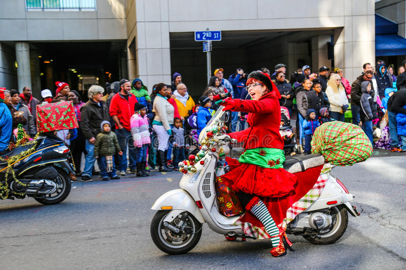 Santa Elves Riding Scooters in Holiday Parade. Harrisburg, PA - November 21, 2015: Elves on scooters on the downtown street in the City of Harrisburg during the stock images