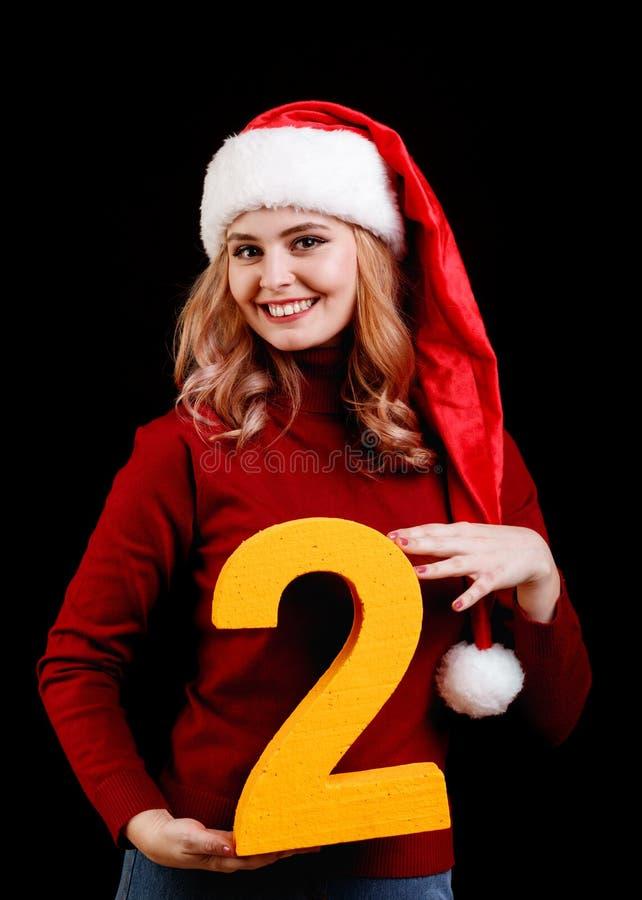 Santa fêmea bonito em um tampão vermelho, guardando o número dois em um fundo preto conceito de um feriado de 2018 anos fotografia de stock