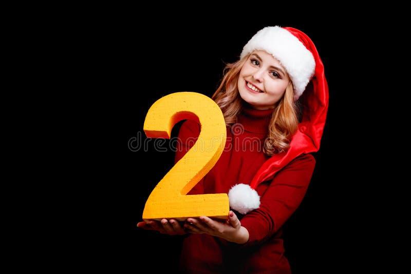 Santa fêmea bonito em um tampão vermelho, guardando o número dois em um fundo preto conceito de um feriado de 2018 anos fotos de stock royalty free