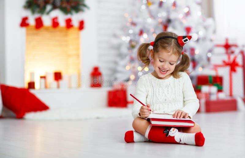 Santa för bokstav för barnflickahandstil hem- near julgran royaltyfria bilder