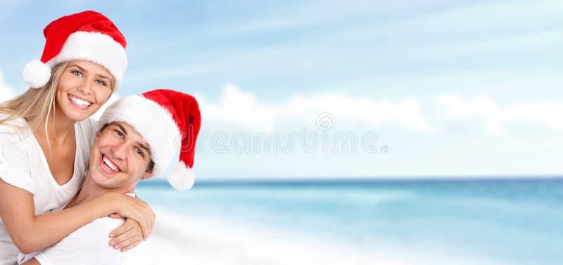 Santa för lycklig jul par på stranden. royaltyfria foton