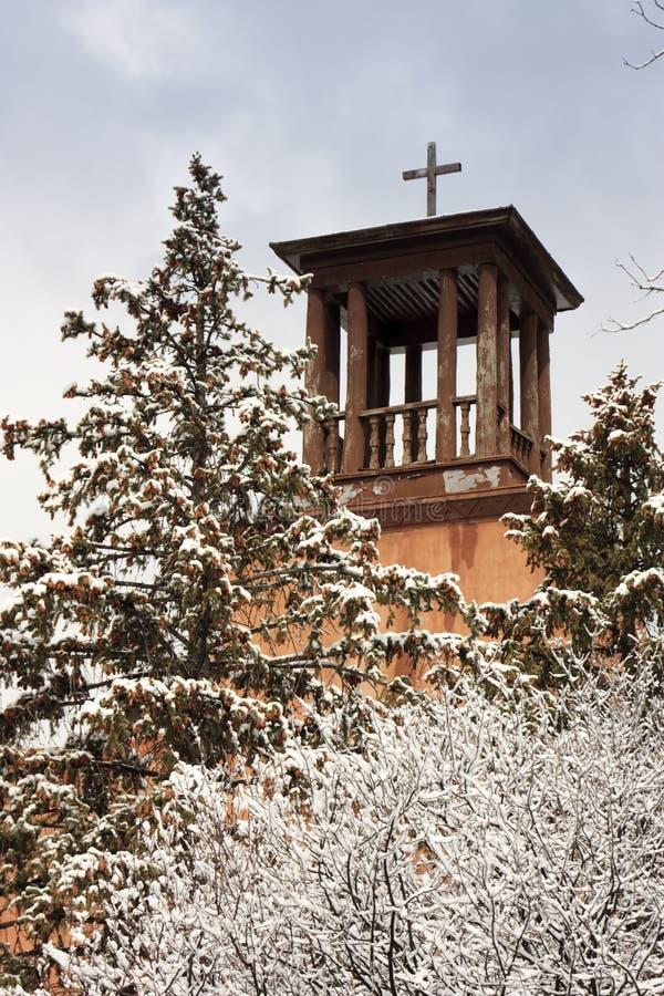 Santa Fe Church Steeple Stands storica sopra gli alberi innevati fotografie stock libere da diritti
