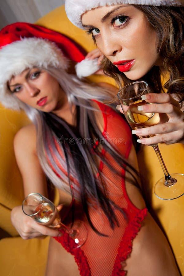 Santa flickor som klirrar exponeringsglas av champagne royaltyfri foto