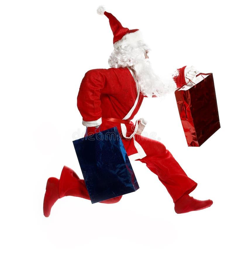 Santa fonctionnante avec des sacs de cadeau photographie stock libre de droits