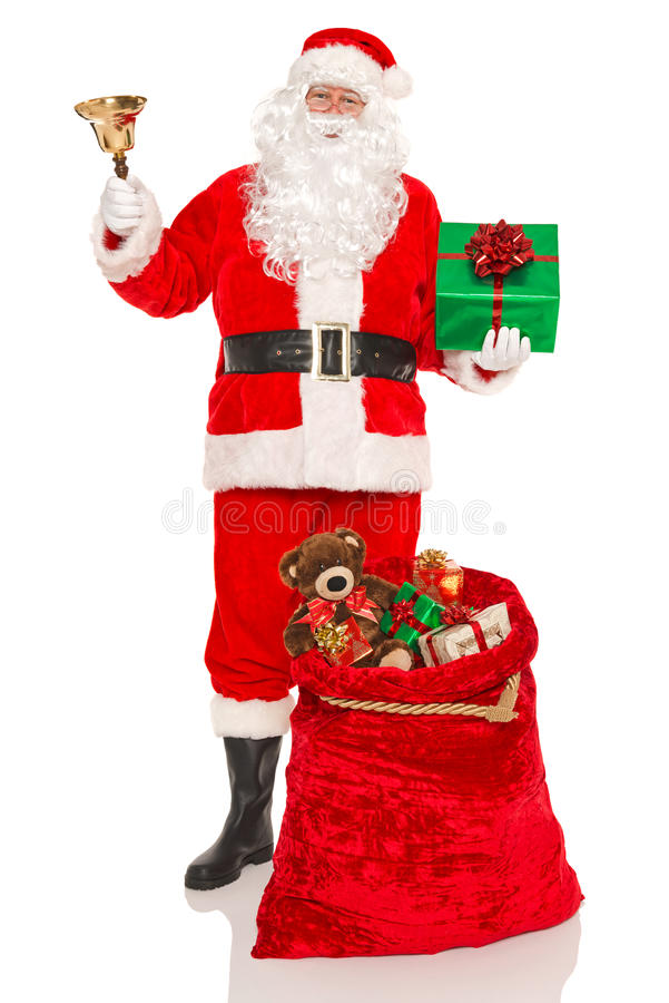 Santa with gifts and a bell. Santa Claus or Father Christmas with a sack full of gifts and holding a bell and gree presnt, isolated on a white background royalty free stock photo