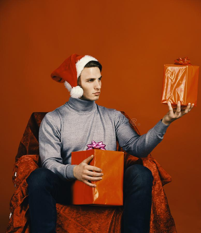 Santa with gifts on red background. Man holds presents. Sitting on red cloth armchair. Serious guy holds red Christmas boxes. Christmas and New Year concept stock photo