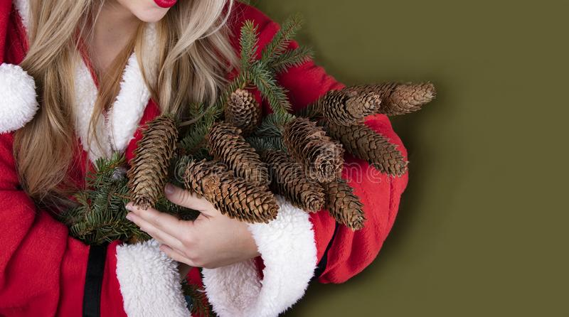 Santa girl with a bouquet of fir branches with cones royalty free stock photo
