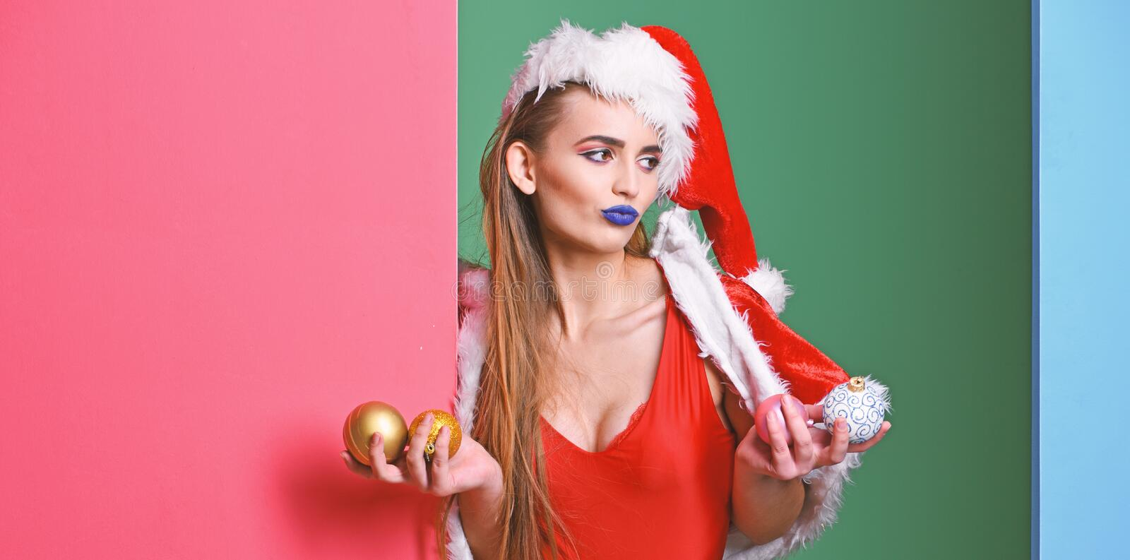 Santa girl christmas party masquerade. Celebrate pool party. Santa girl sexy with make up. Girl red swimsuit and santa. Hat hold christmas ball decoration royalty free stock photo