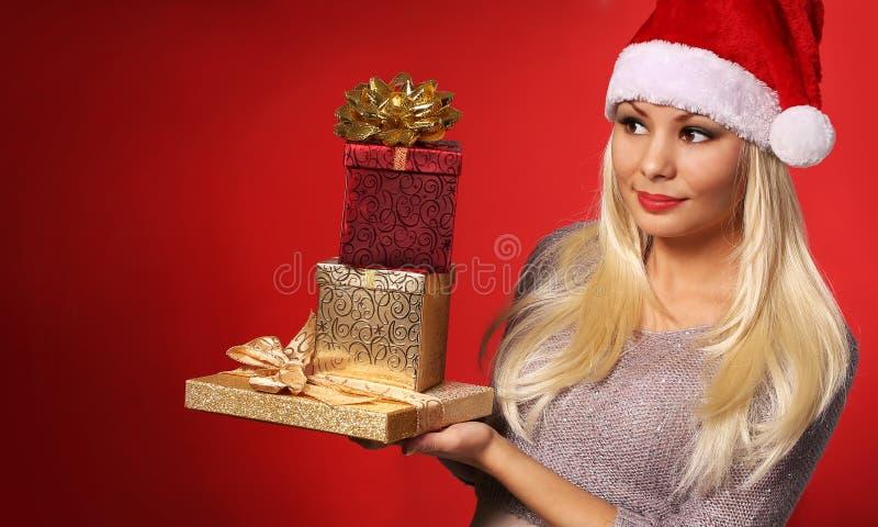 Santa Girl con las cajas de regalo sobre fondo rojo Navidad imagenes de archivo