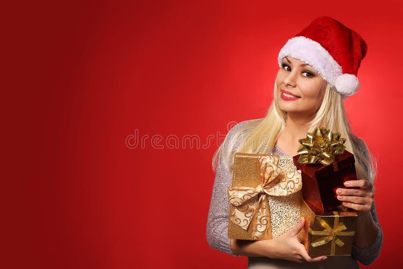 Santa Girl con las cajas de regalo sobre fondo rojo Navidad imagen de archivo
