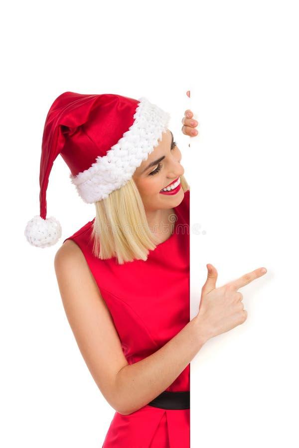 Santa Girl rubia que señala en el cartel fotografía de archivo libre de regalías