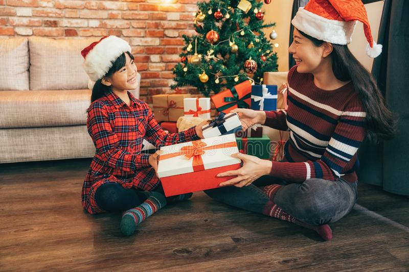 Santa girls exchanging gift on Xmas Eve. Young mother and her daughters on the wood floor by christmas tree at home. attractive santa girls exchanging gift in royalty free stock photos