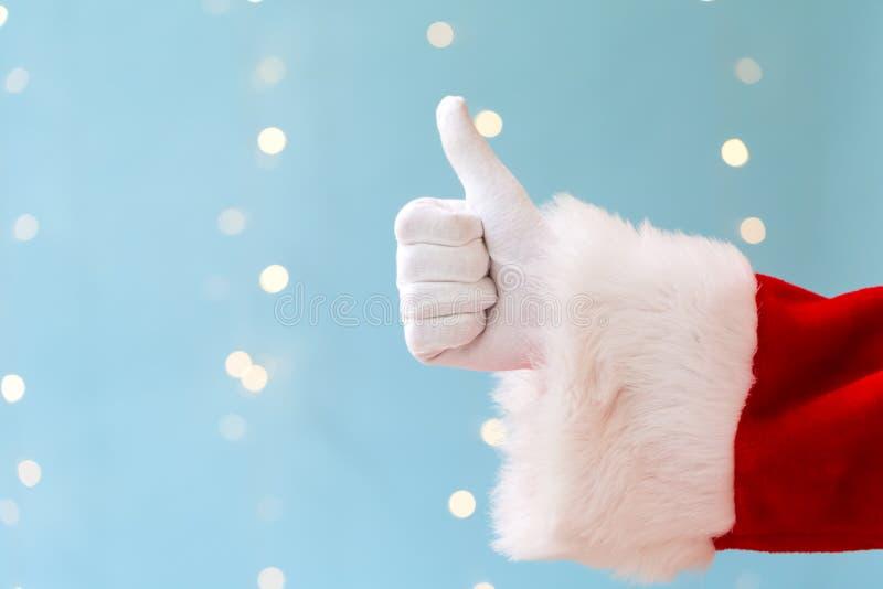 Santa giving thumb up. On a shiny light blue background royalty free stock photo
