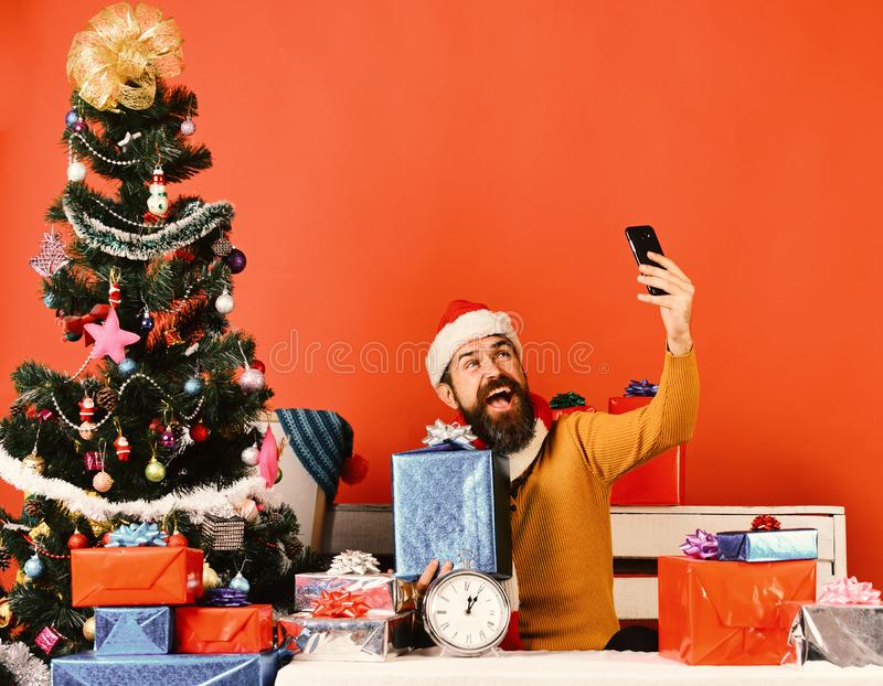 Santa guarda o telefone celular e a caixa atual Homem com barba imagens de stock