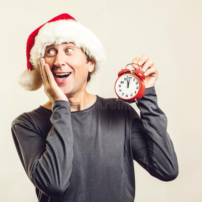 Santa guy holding red clock, isolated on white. Worried man wearing Santa Claus helper hat. Time is coming. New Year and Christmas stock photography
