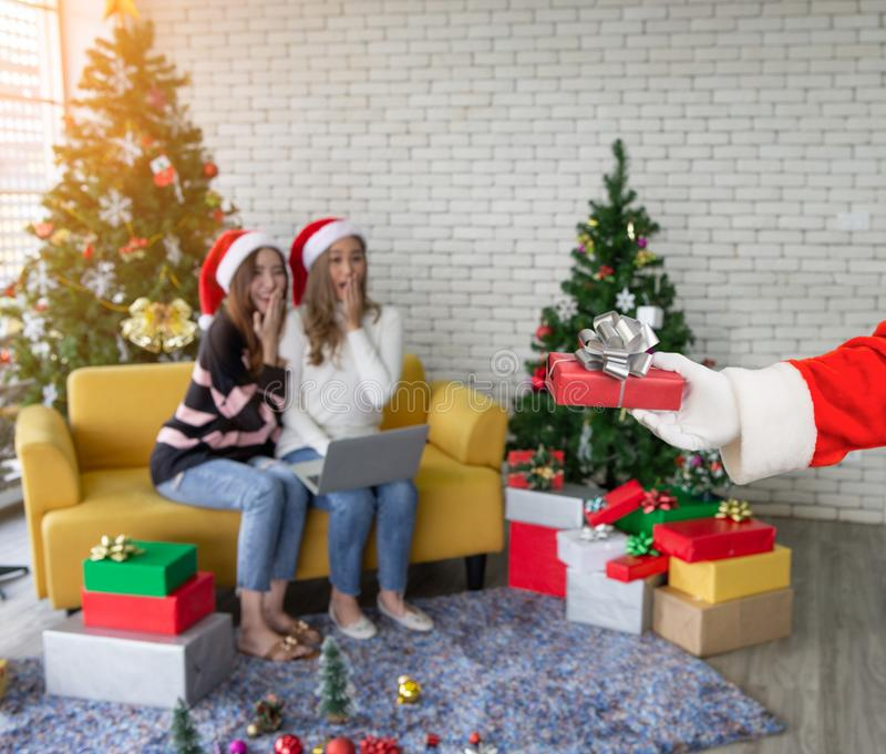 Santa hand holding and giving red gift box beautiful two women in christmas party stock image