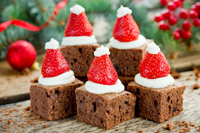 Santa hat brownie, Christmas dessert, chocolate pieces with strawberry and cream royalty free stock photography