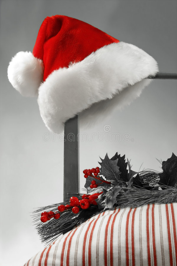 Santa Hat on a chair. Santa hat hanging on the side of a chair Selective B/W royalty free stock photo