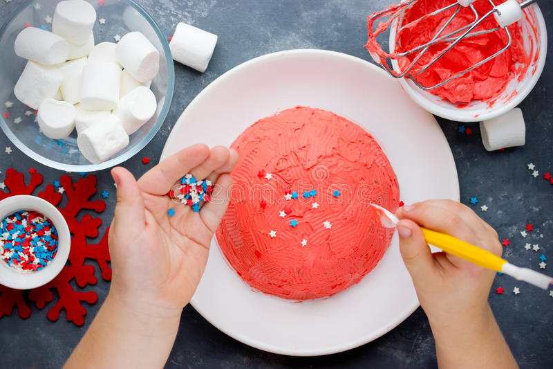 Santa hat Christmas cake. Winter hat cake with traditional ornament decoration. Child hands cooking New Year dessert, Christmas t royalty free stock photography